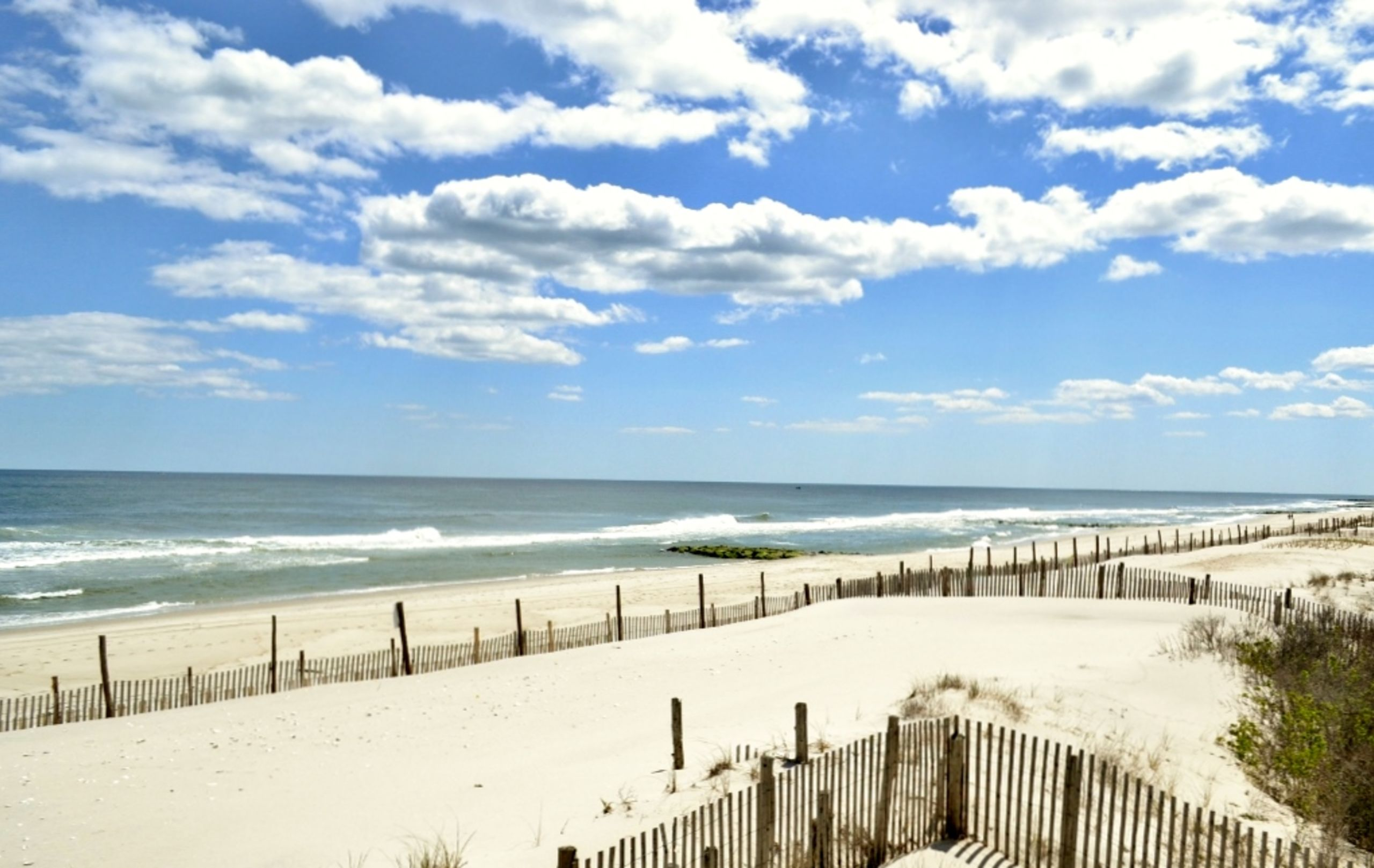 Where the white sands meet the blue sea under powder puff clouds