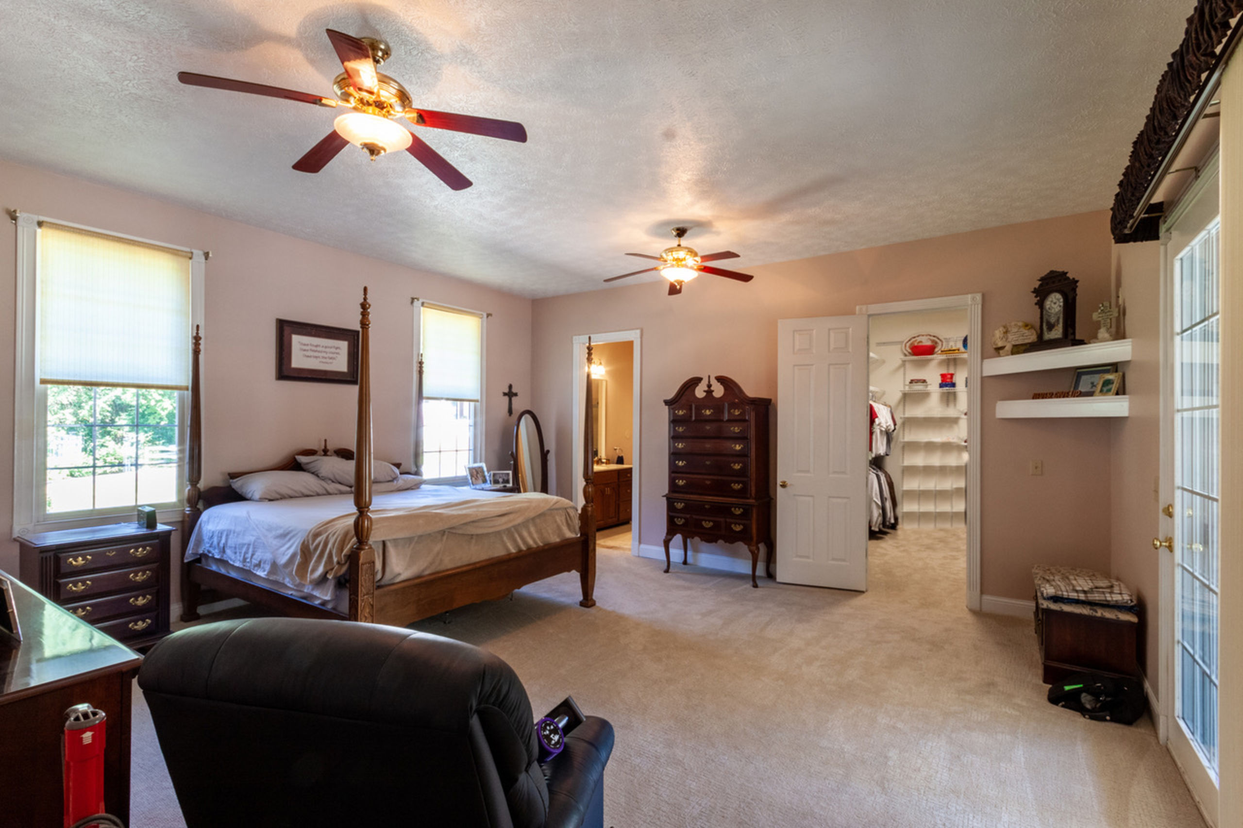 Massive primary bedroom w/large en-suite, huge walk-in closet & private patio/pool access